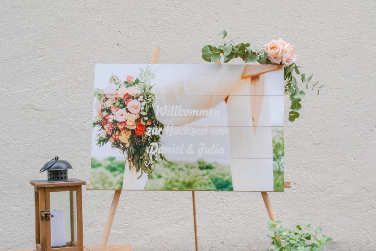 Pixum Foto auf Holz als Hochzeits-Willkommenstafel auf einer Staffelei und mit Blumen geschmückt