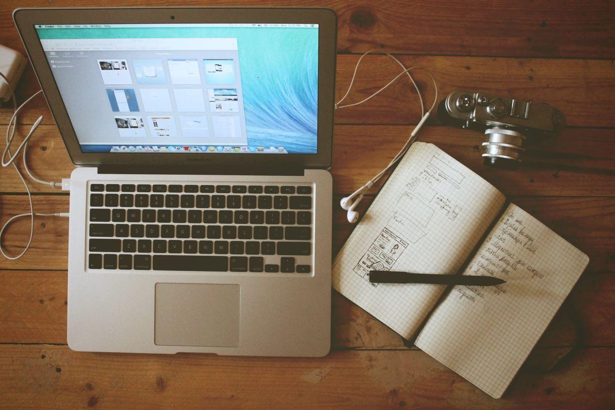 Offener Laptop mit aufgeschlagenen Notizbuch auf einem Tisch.