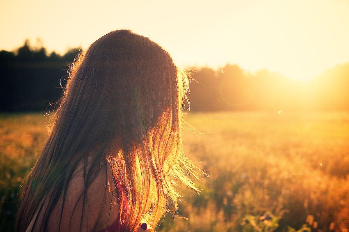 Frau sieht in den Sonnenuntergang.