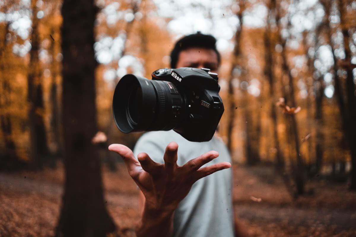 Spiegelreflex-Kamera schwebt im herbstlichen Ambiente über der Hand eines Mannes.