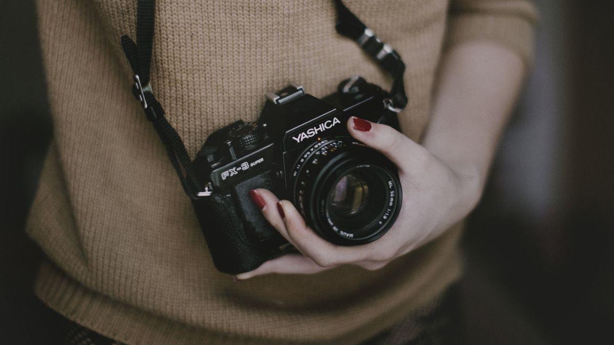 Frau hält Kamera in der Hand.