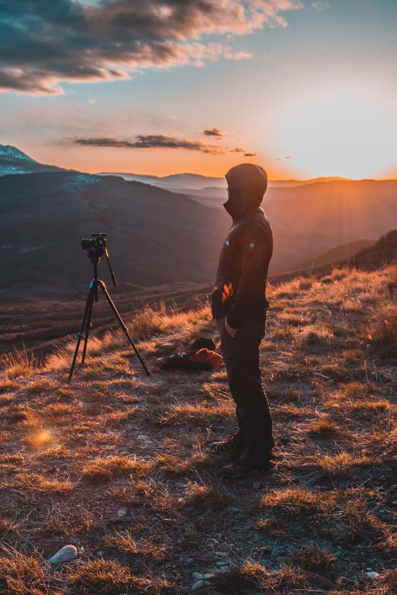 Mann mit Kamerastativ in den Bergen.