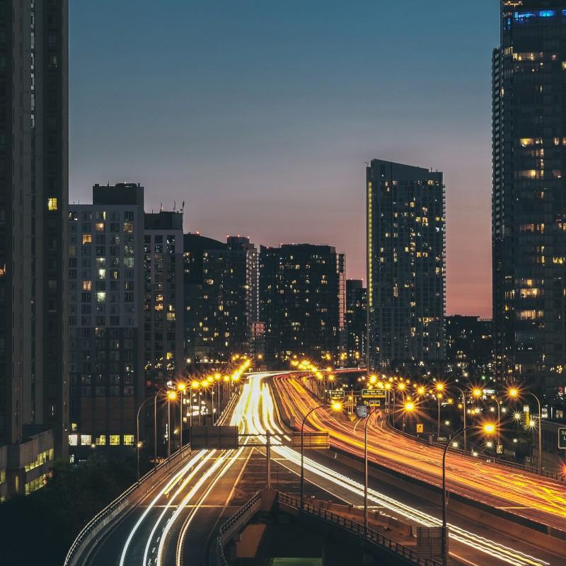 Stadt bei Nacht mit Straßenverkehr.
