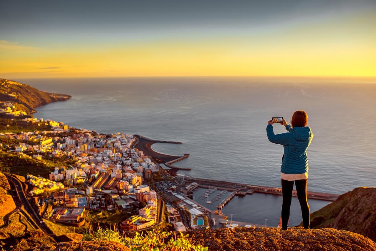 Eine Frau steht mit ihrem Handy auf dem Berg vor einer Stadt am Meer und fotografiert die Stadt, die vom Sonnenuntergang in goldenes Licht gehüllt wird.