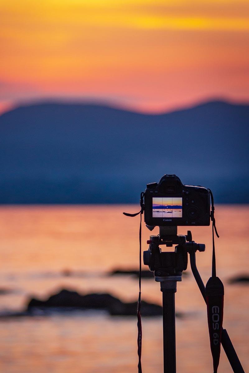 Kamera steckt auf einem Stativ und ist in Richtung Sonnenuntergang aufgestellt. Das Kamera Display zeigt die Live-Aufnahme des Fotos.