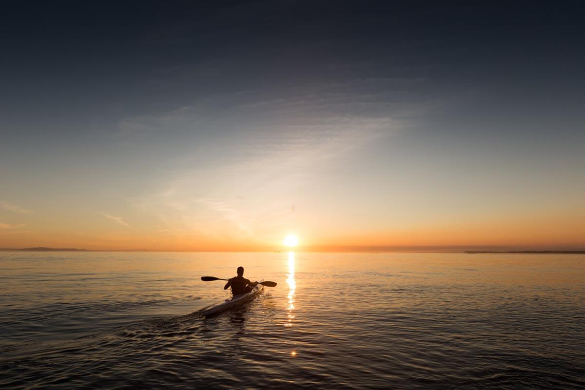 Ein Mann sitzt im Kanu und paddelt auf ruhiger See dem Horizont entgegen, wo gerade die Sonne untergeht. Die Spiegelung der Sonne im Meer taucht das Bild in ein warmes Licht.