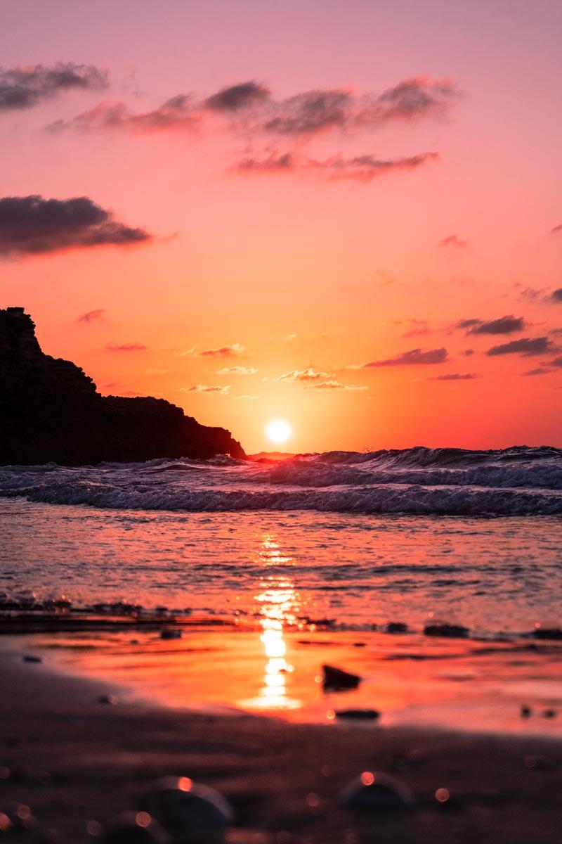 Die Sonne steht tief über dem Meer und taucht den Himmel in pinke Farben.