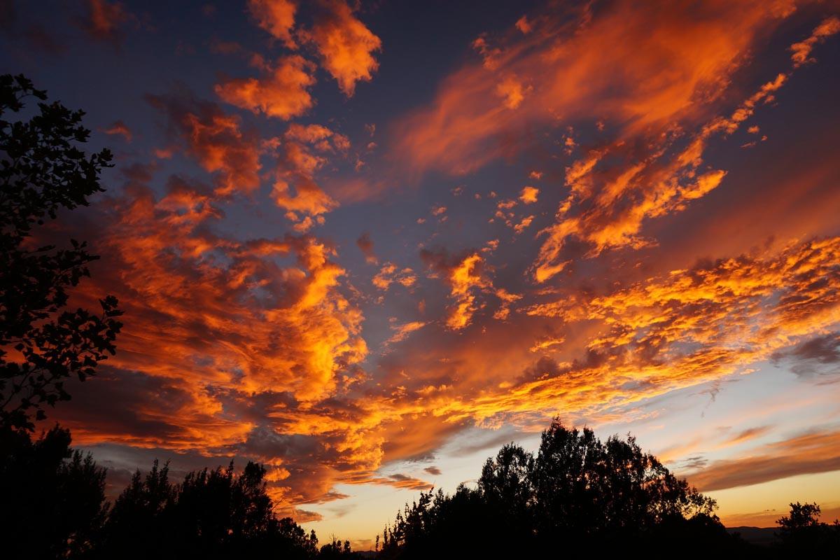 Die Sonne verschwindet hinter dem Horizont und färbt die Wolken in ein feuriges Orange. Die Struktur der Wolken macht das Bild zu etwas ganz Besonderem.