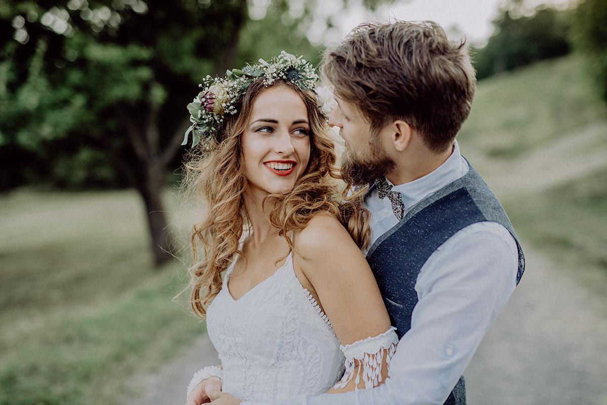 Junges Brautpaar umarmt sich lächelnd.
