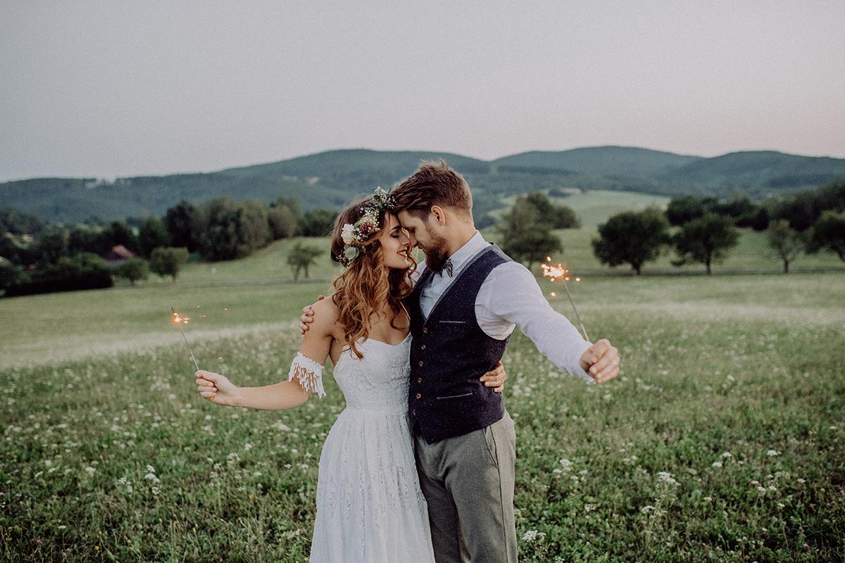 Junges Brautpaar hält Wunderkerzen in der Hand.