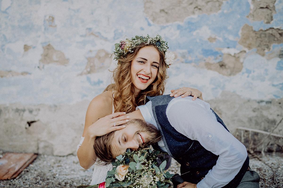 Brautpaar albert rum vor einer Steinwand.