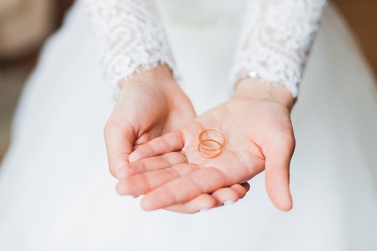 Braut hält die Eheringe in den Handflächen.