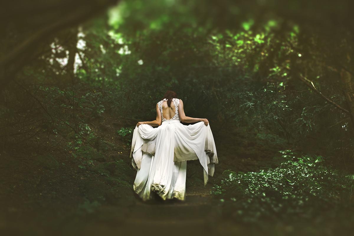 Eine Braut mit zerstörtem Brautkleid im Wald.