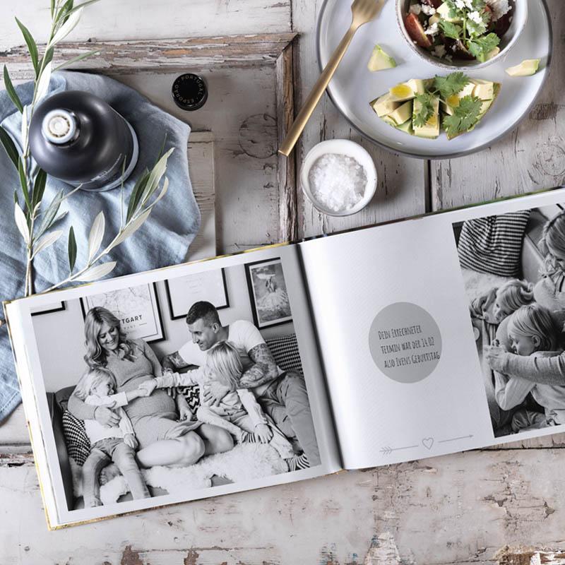 Pixum Fotobuch liegt aufgeklappt auf einem Tisch.