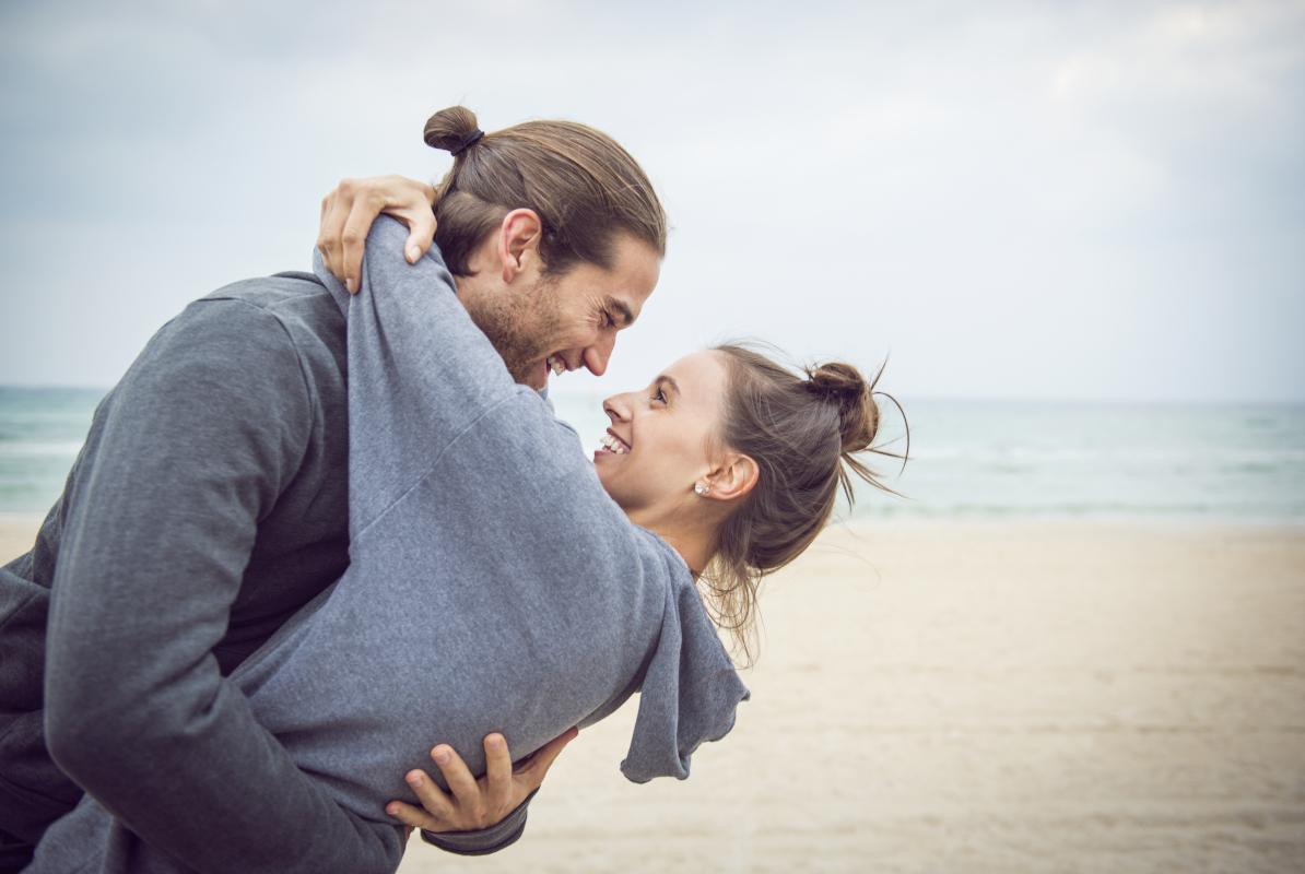 Lachendes Pärchen umarmend am Strand.