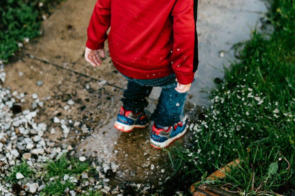 Kind springt in eine Pfütze.