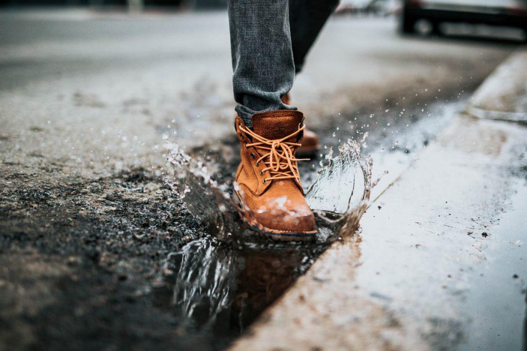 Fuß steht in einer Pfütze und Wasser spritzt hoch.