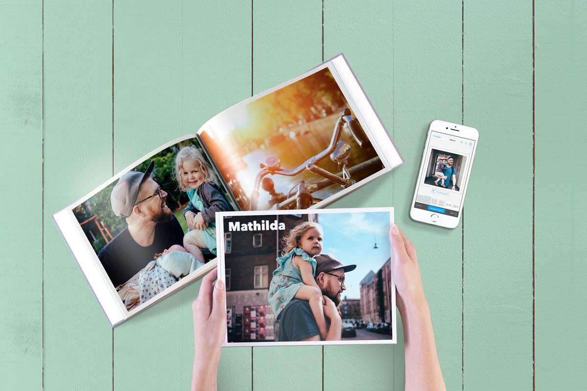 Fotobuch und Smartphone liegen auf dem Tisch.
