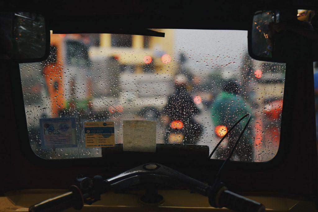 Regentropfen auf Fensterscheibe mit Bokeh im Hintergrund.