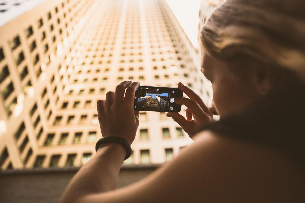 Frau fotografiert ein Gebäude mit dem Smartphone