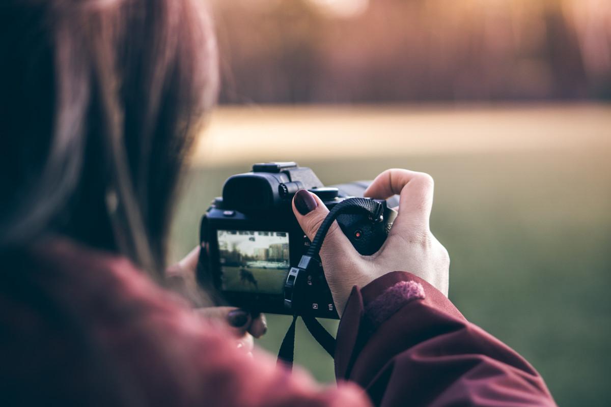 Frau fotografiert mit Spiegelreflex