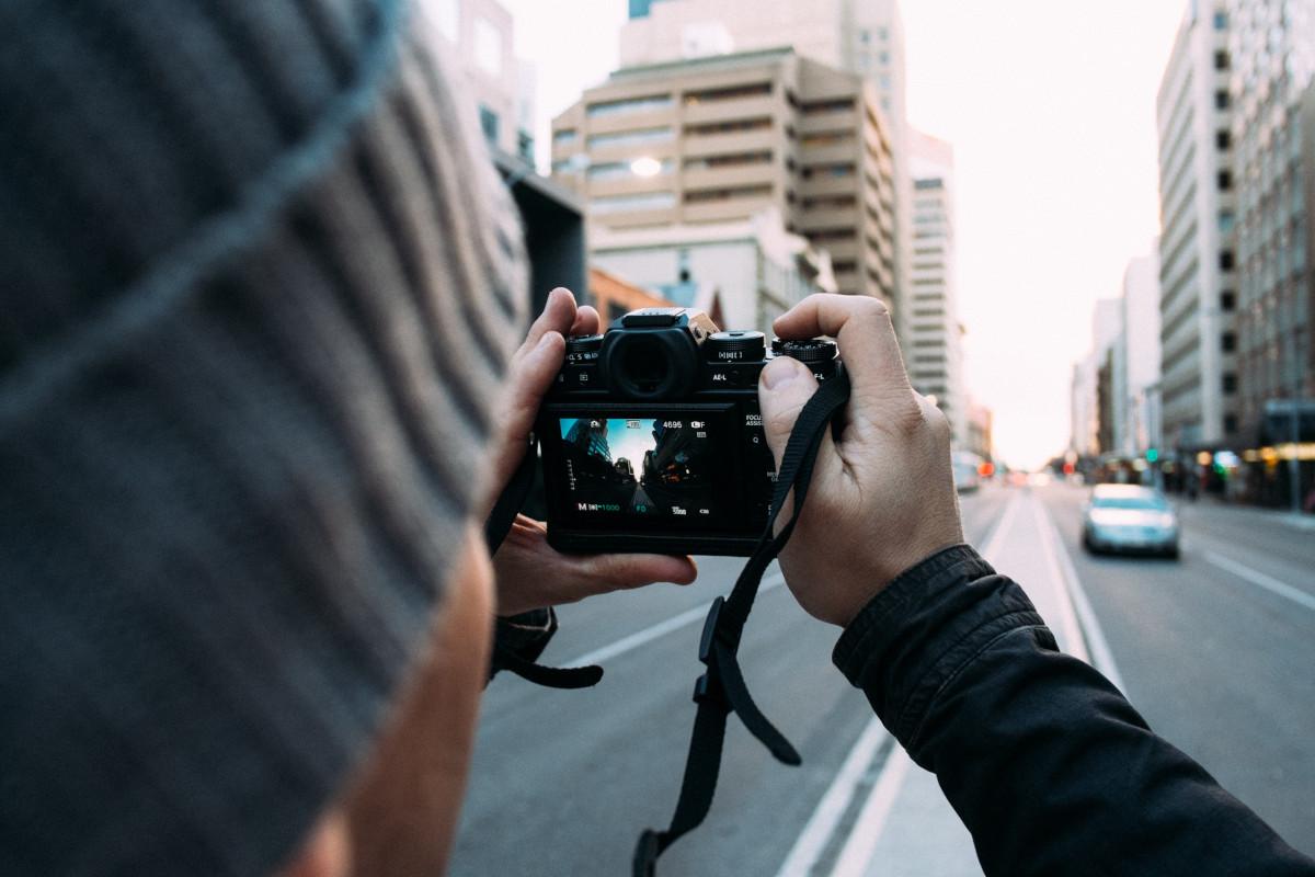 Mann hält Kamera zum Fotografieren