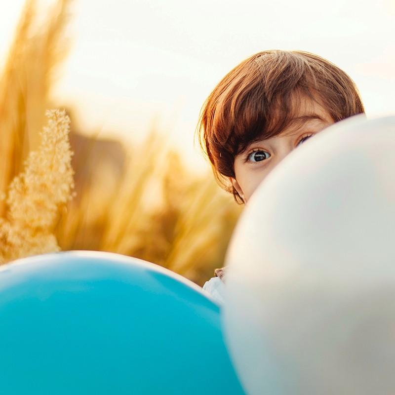 Kind versteckt sich hinter Ballons.