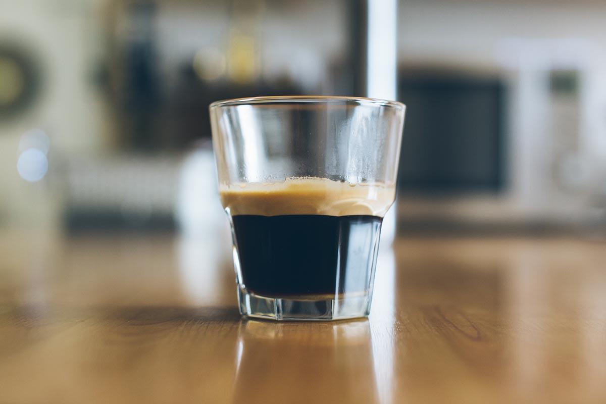 Ein Glas mit Kaffee steht auf dem Tisch.