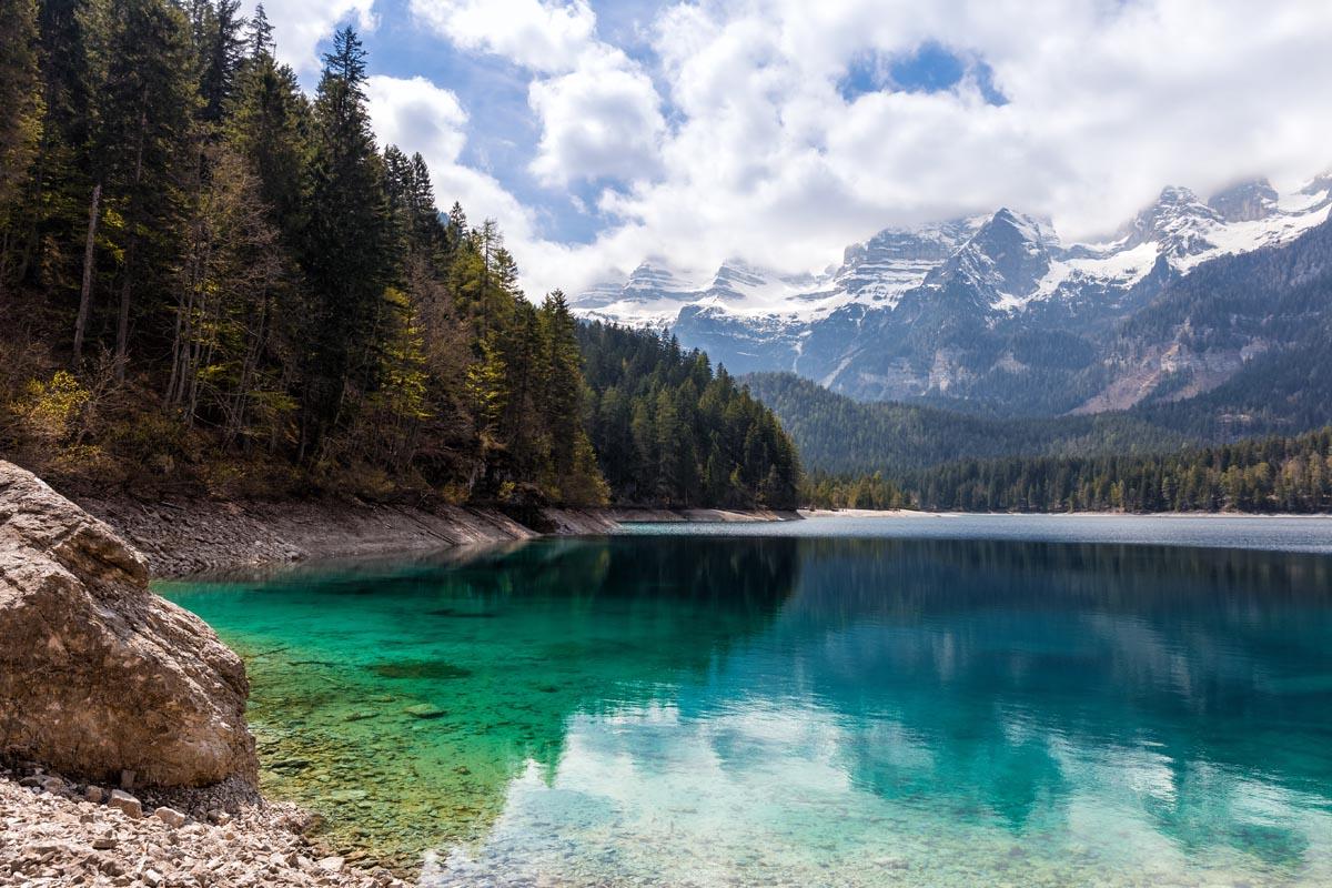 Türkisfarbener See vor einer Berglandschaft.