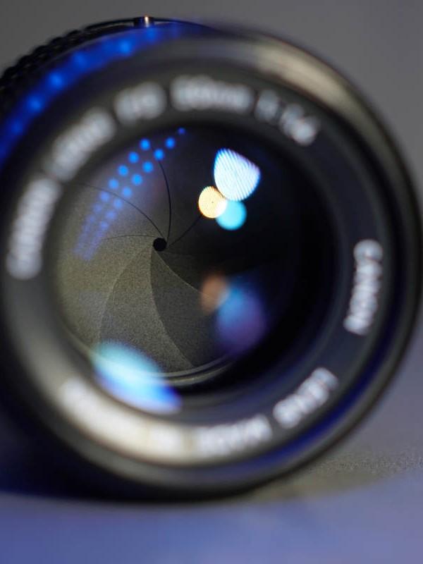 Kameraobjektiv mit geschlossener Blende auf einem Tisch.