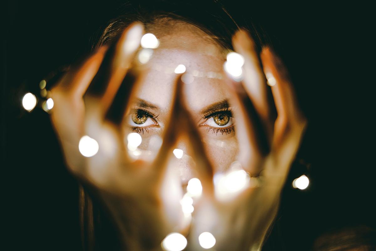 Frau mit Lichterkette im Dunkeln.