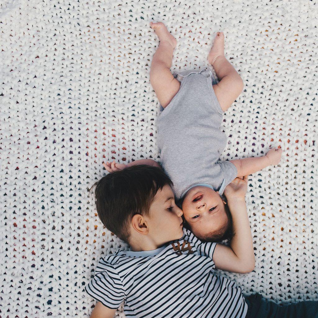 Bruder und Baby auf einer Decke.
