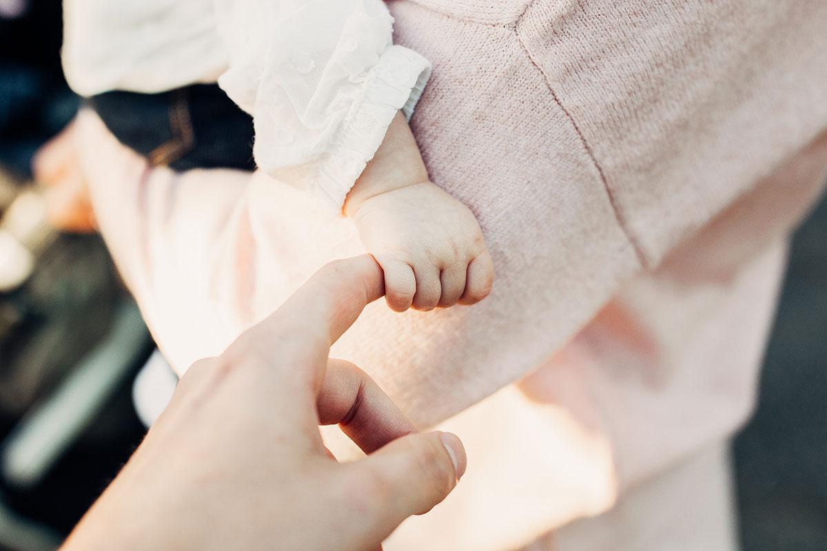 Baby auf Arm hält Hand des Fotografen