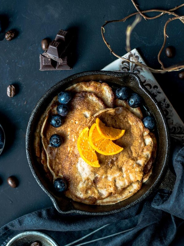 Pfanne mit Pancakes, Blaubeeren und Orangen steht hübsch angerichtet auf blauem Untergrund