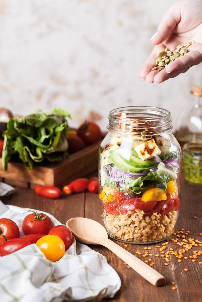 Eine Hand schüttet die letzten Zutaten für einen Salat im Glas hinein. Auf dem Tisch liegen diverse frische Zitaten.