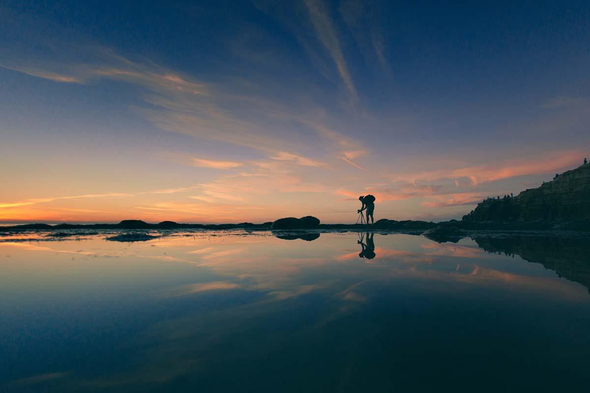 Mann fotografiert die Spiegelung im Wasser.