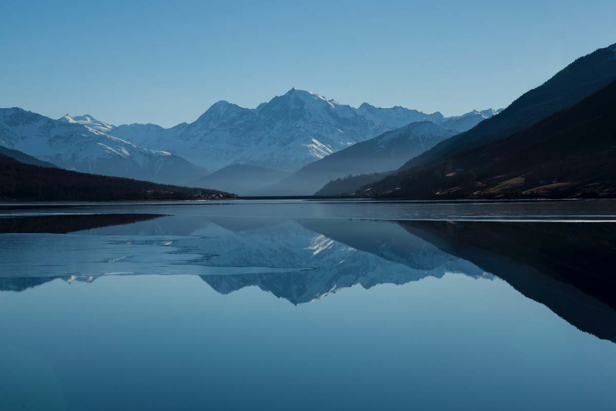 Berge spiegeln sich im See.