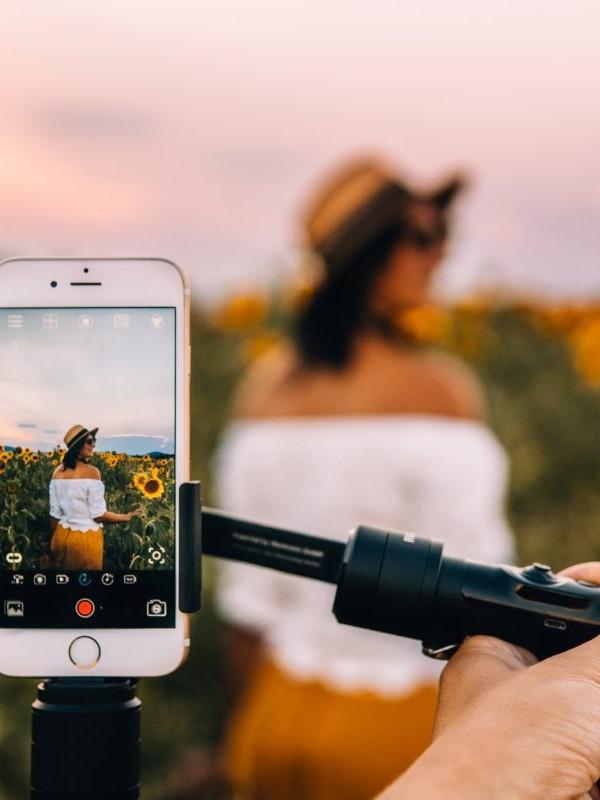 Jana steht in einem Sonnenblumenfeld mit ihrem Smartphone bei der Reisefotografie