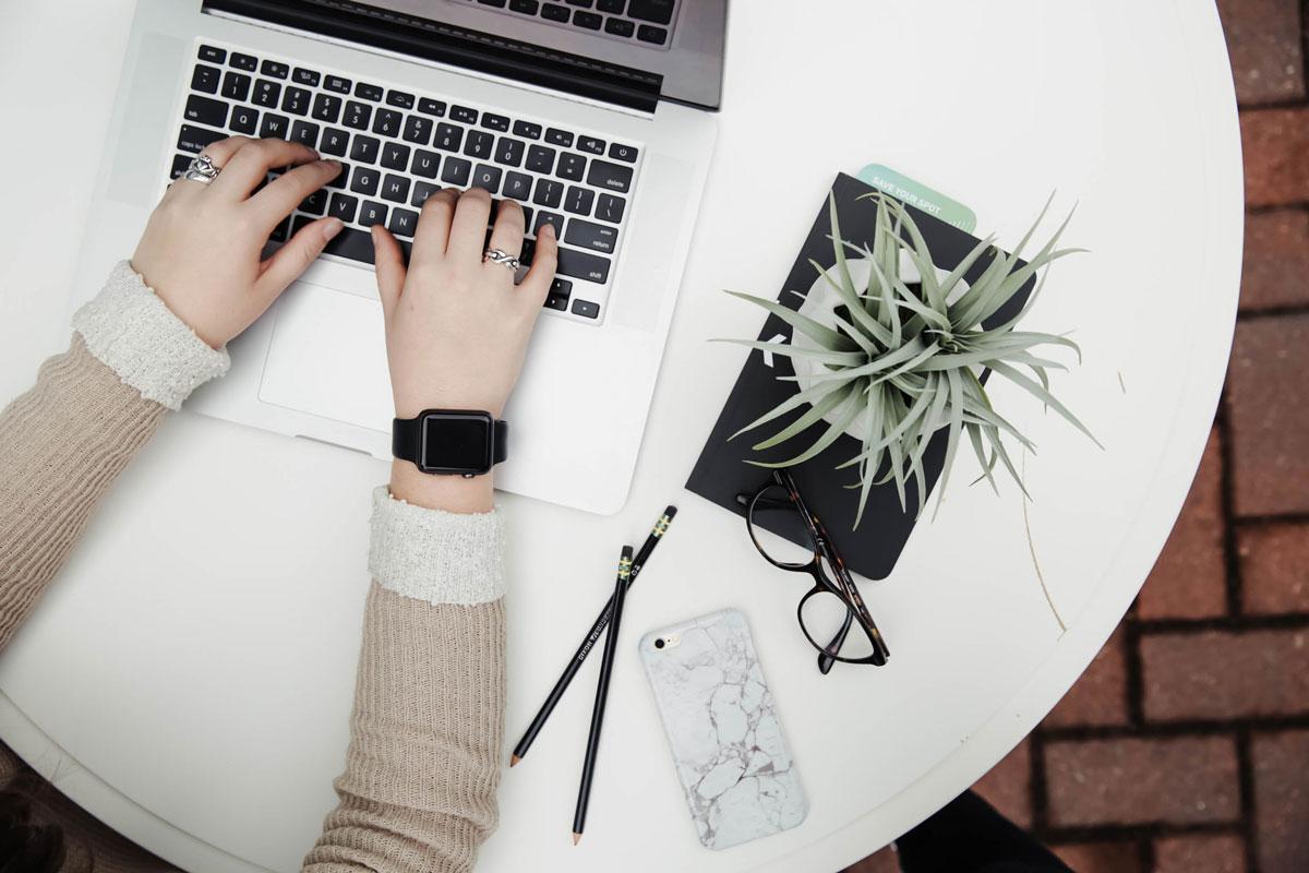Auf einem Tisch liegen ein Smartphone, eine Brille, Pinsel, Notizbücher und eine Pflanze. An dem Laptop direkt daneben arbeitet eine Frau.