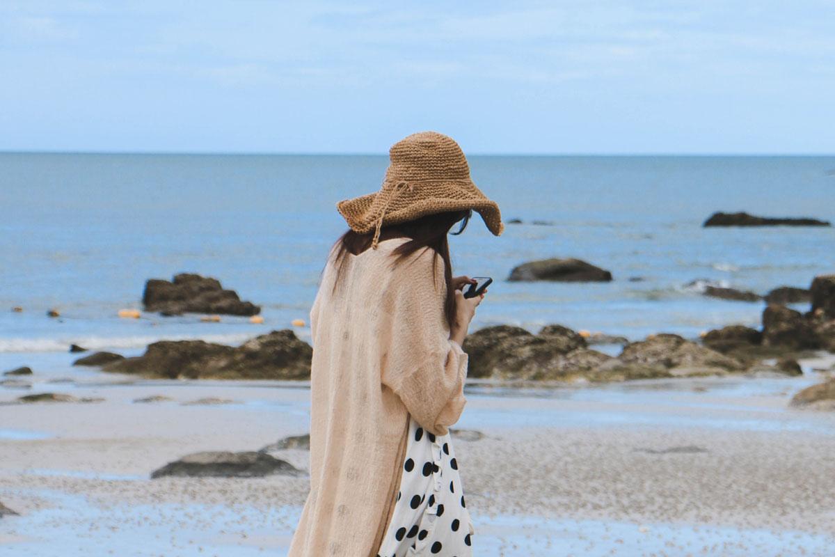 Eine Frau hält im Urlaub am Strand ihr Smartphone in der Hand.