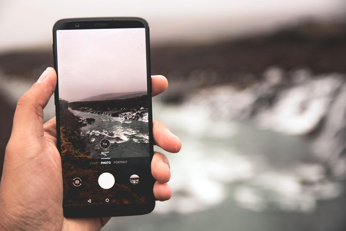 Eine Hand hält ein Smartphone, mit dem ein Fluss fotografiert wird. Es ist ein grauer, nebliger Tag, was sich gut für Reisefotografie eignet.