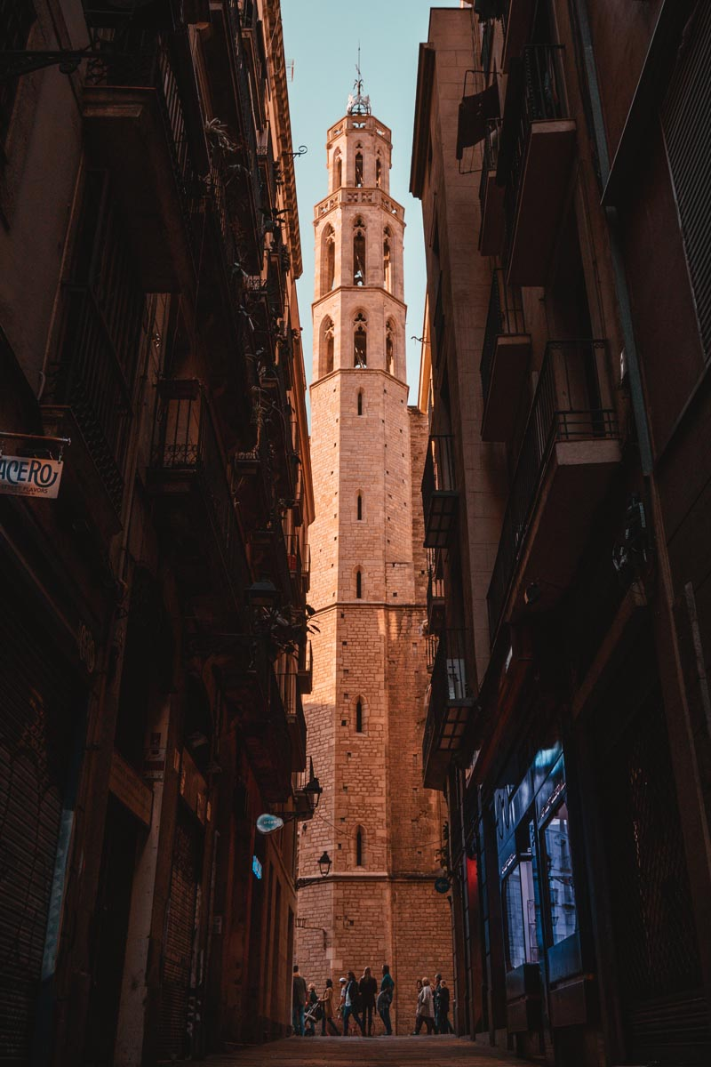 Blick auf einen Turm durch eine schmale Gasse