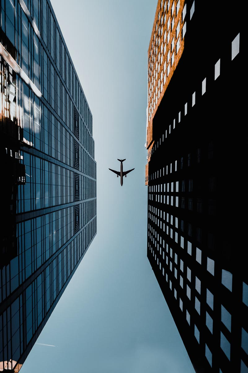 ein Flugzeug fliegt über einer Großstadt und ist durch zwei große Häuser zu erspähen