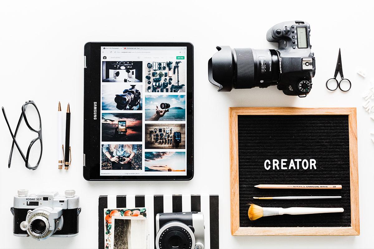 Verschiedenes Fotoequipment liegt auf einem Tisch. Ein Kreativ-Arbeitsplatz.