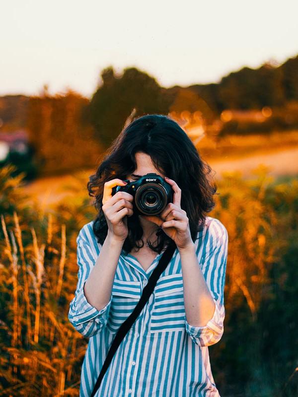 Eine Frau steht im Sommer auf einem Feld und fotografiert. Die schönste Beschäftigung fürs lange Wochenende.