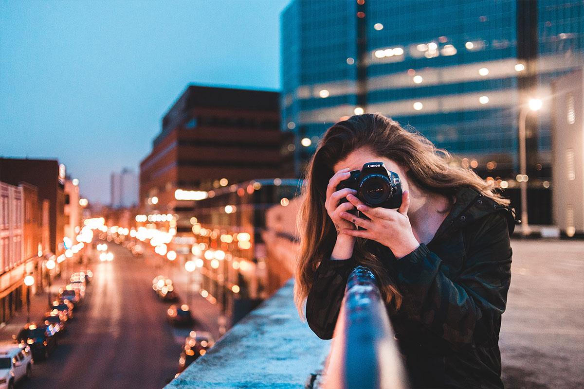 Eine Frau macht an ein Geländer gelehnt Fotos von der Großstadt.