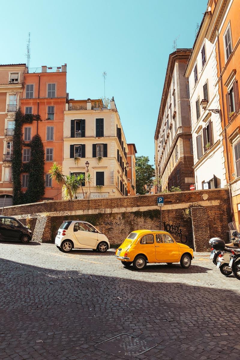 Parkende Autos vor einer Gasse in Italien