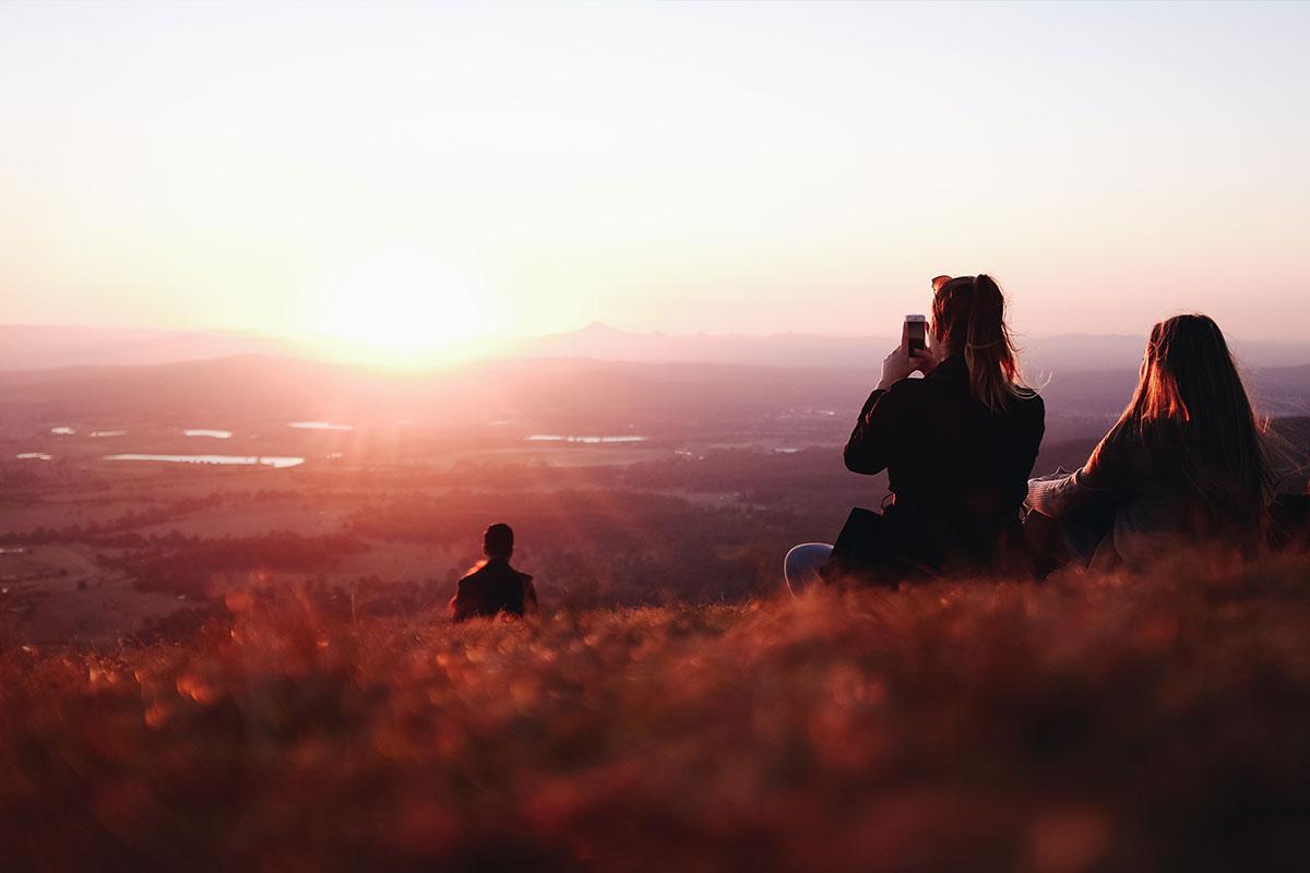 Zwei Mädchen sitzen als Finale ihres langen Wochenendes auf einem Hügel mit einem traumhaften Sonnenuntergang. Eine von ihnen nutzt die Chance, um Smartphone-Fotos zu machen,
