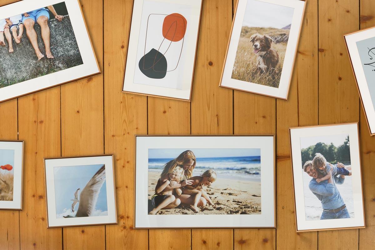 Die Auswahl an Bildern im Rahmen für eine Fotowand liegen auf dem Boden aus