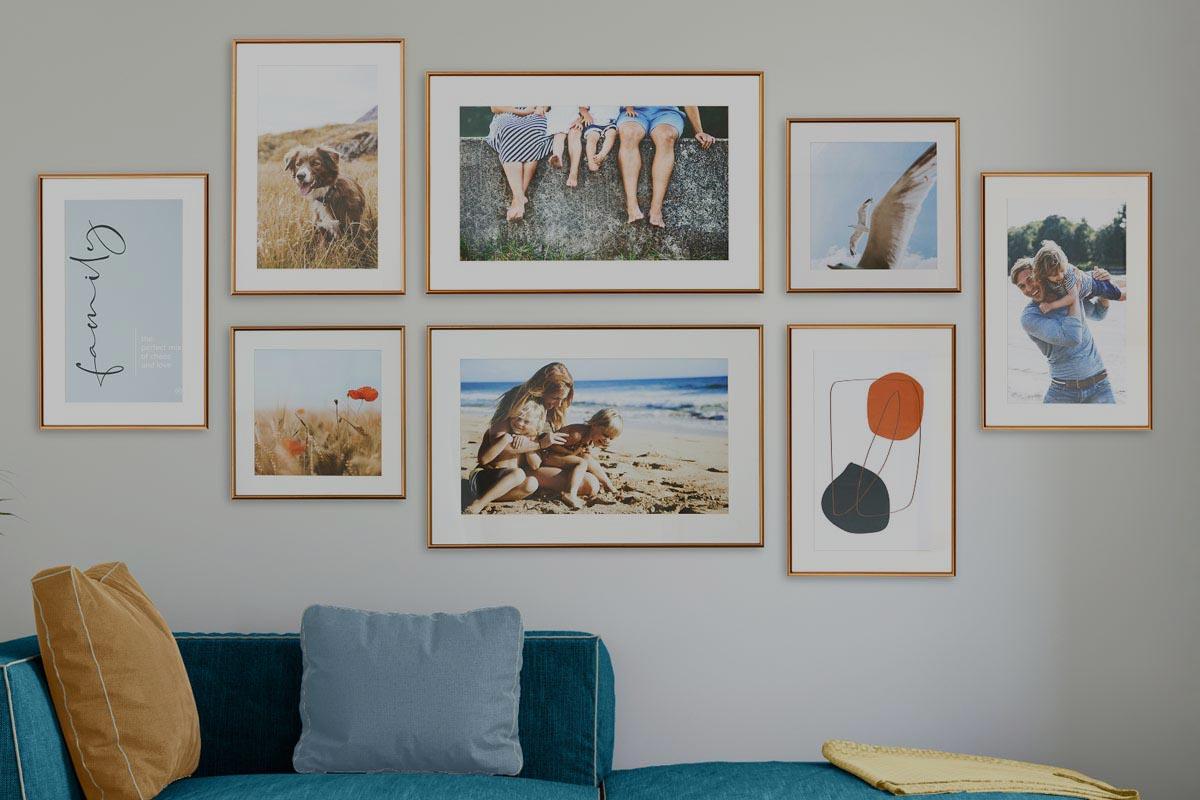 Acht Bilder hängen an der Wand über einem Sofa